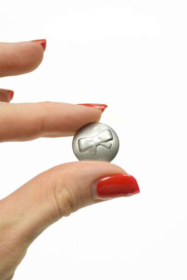 Пуговица металл серебро с выбитым бантиком 3