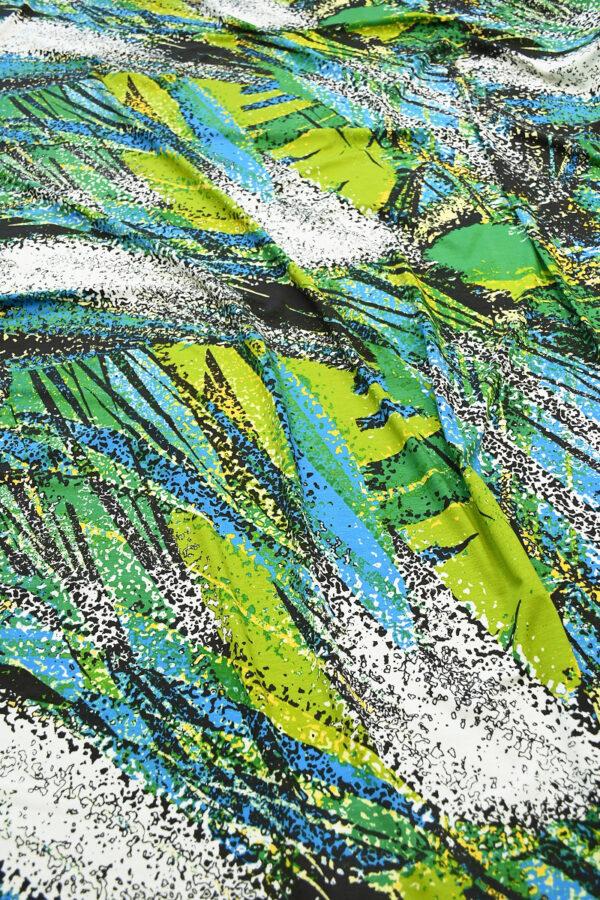 Трикотаж с крупными пальмовыми листьями. Рисунок стилизованный, яркий, выполнен в зеленых и голубых тонах в сочетании с черным и белым.